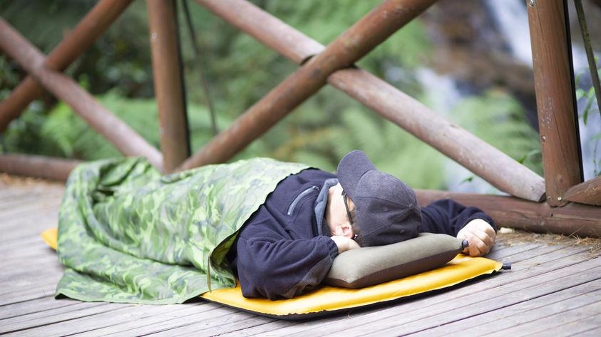 Mann schläft auf selbstaufblasbarer Isomatte